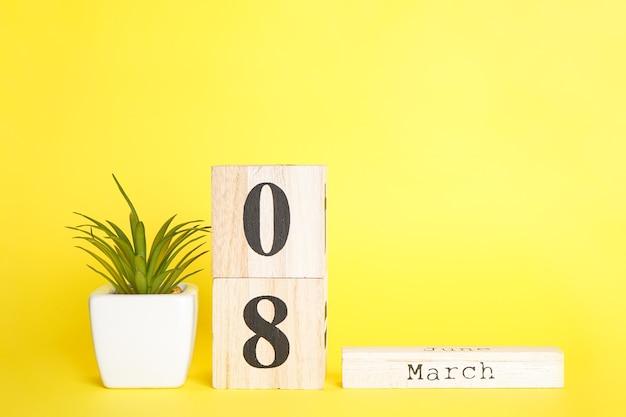 Calendrier en bois du 8 mars composition à plat avec plante succulente