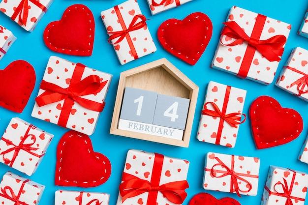 Calendrier en bois entouré de coffrets cadeaux avec coeurs papier d'emballage et coeurs textile
