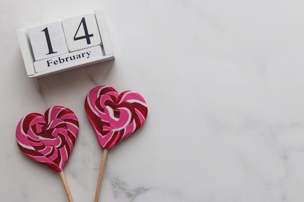 Calendrier en bois février et bonbons en forme de coeur sur marbre