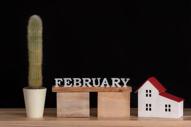 Calendrier en bois de février, cactus et modèle de maison sur fond noir. espace de copie