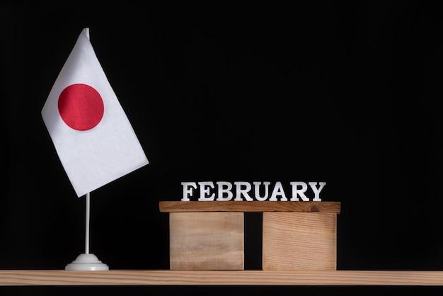 Calendrier en bois de février avec drapeau du japon sur mur noir