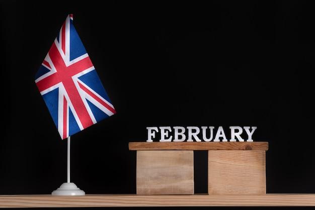 Calendrier en bois de février avec drapeau de la grande-bretagne sur fond noir
