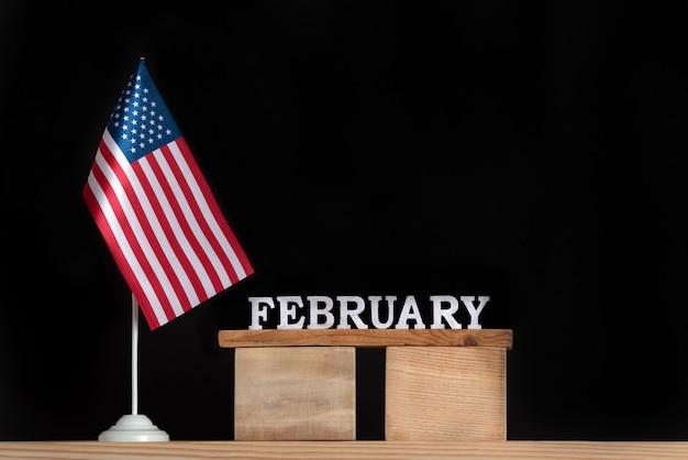 Calendrier en bois de février avec drapeau usa sur fond noir