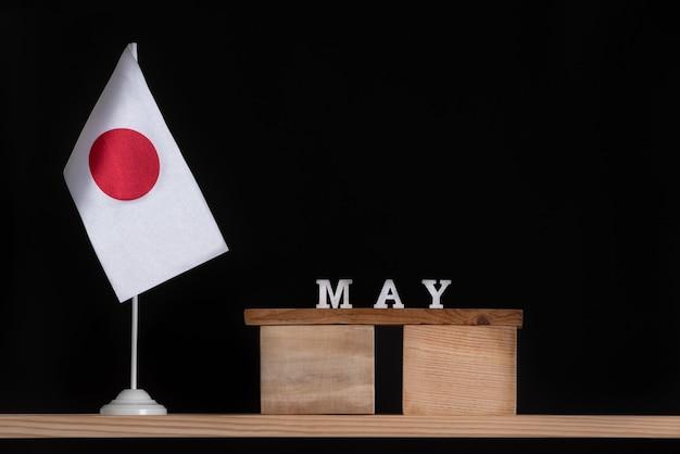 Calendrier en bois de mai avec table drapeau japonais sur fond noir. fêtes du japon en mai.