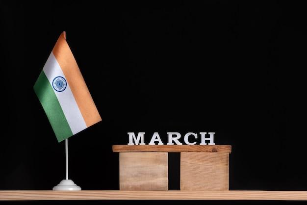 Calendrier en bois de mars avec drapeau indien sur fond noir