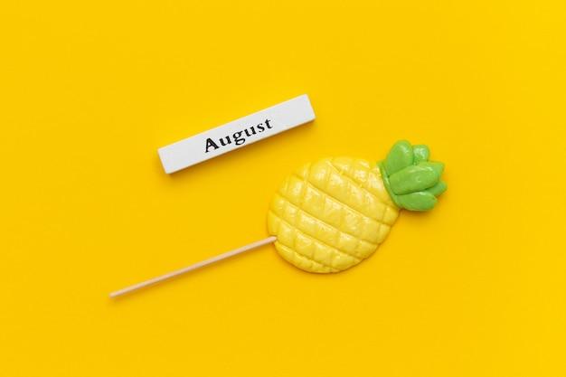 Calendrier en bois mois d'été août et sucette d'ananas sur bâton sur fond jaune