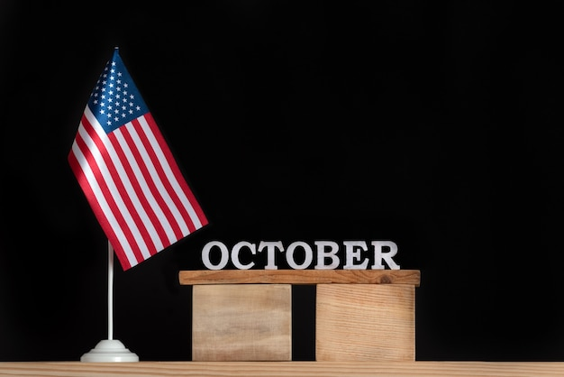 Calendrier en bois pour octobre avec drapeau usa sur mur noir