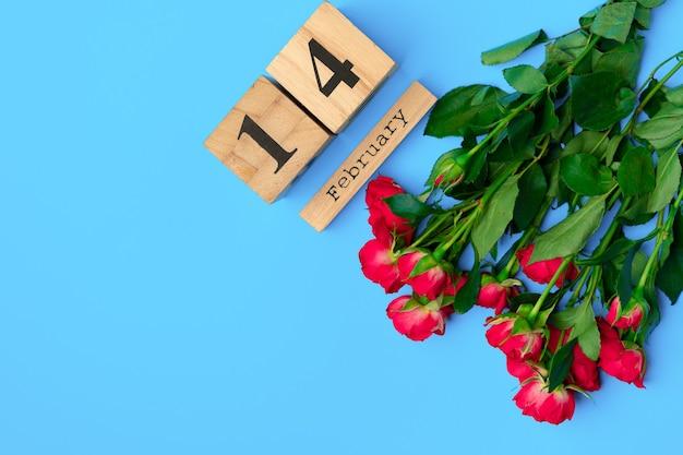 Calendrier en bois et roses sur fond bleu vue de dessus