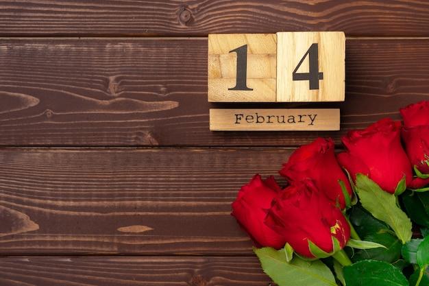 Calendrier en bois et roses sur fond de bois marron