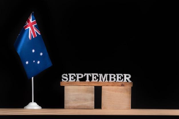 Calendrier en bois de septembre avec drapeau australien sur surface noire. vacances de l'australie en septembre.