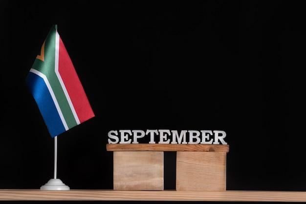 Calendrier en bois de septembre avec drapeau rsa sur fond noir. dates de l'afrique du sud en septembre.