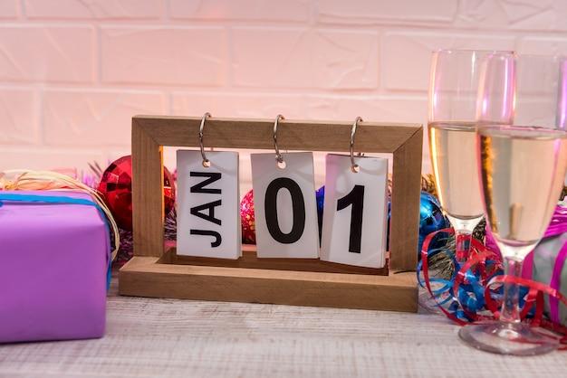 Calendrier en bois avec verres de champagne et décorations du nouvel an sur table en bois