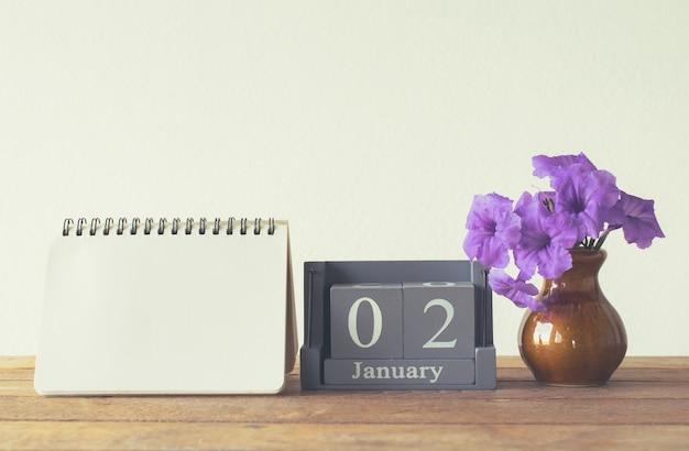 Calendrier en bois vintage pour le jour de janvier 2 sur une table en bois avec espace vide pour livre de notes pour le texte.