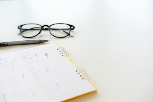 Calendrier calendrier arrière-plan avec un stylo et des lunettes pour planifier les travaux dans la résolution de la nouvelle année 2020