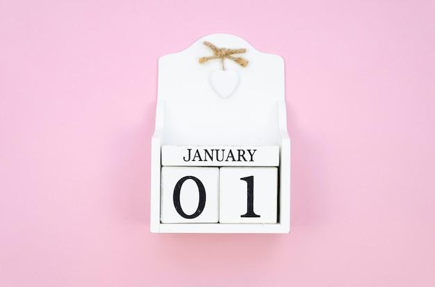 Calendrier de cube en bois blanc vue de dessus 01 janvier sur fond rose.