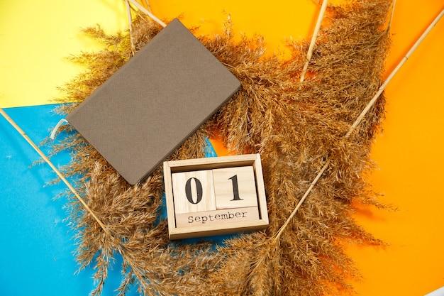 Calendrier de cubes en bois avec chiffres et mois. bloc-notes avec des draps blancs. le premier jour de l'année scolaire. choisir un nombre sur un calendrier en bois. 1er septembre. date de septembre