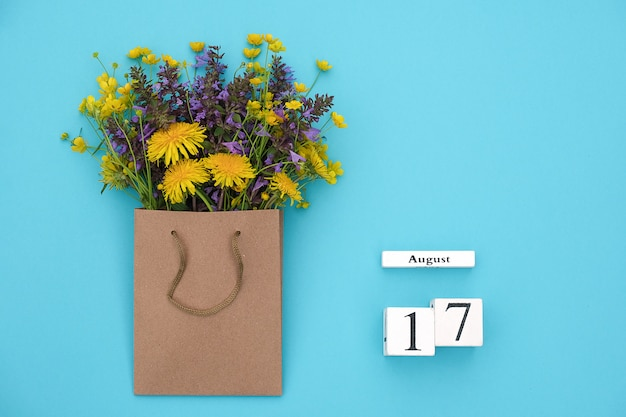 Calendrier de cubes en bois du 17 août et champ de fleurs rustiques colorées dans un emballage artisanal