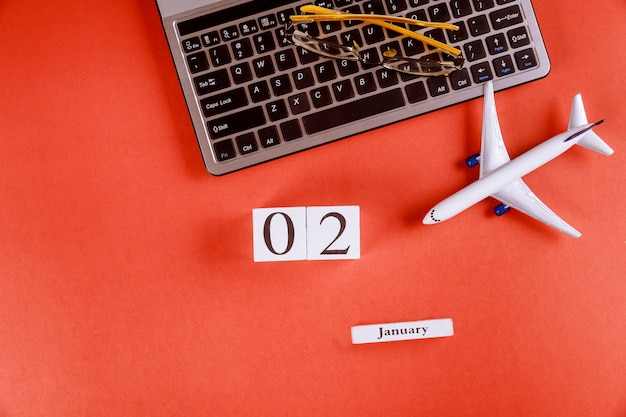 Calendrier du 02 janvier avec des accessoires sur le bureau de bureau de l'espace de travail sur le clavier de l'ordinateur, avion, fond rouge de lunettes