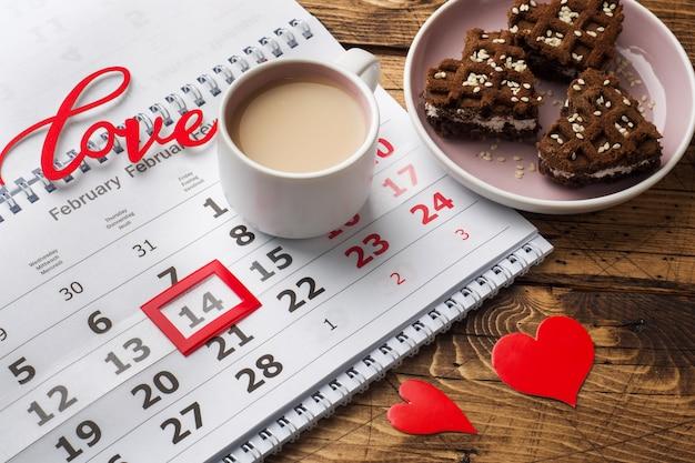 Calendrier du 14 février. concept de la saint-valentin, coeurs rouges, le mot amour et une tasse de café.