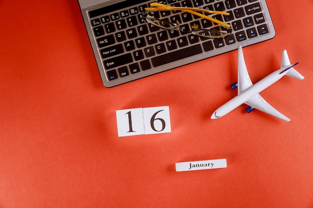 Calendrier du 16 janvier avec accessoires sur le bureau de bureau de l'espace de travail sur le clavier de l'ordinateur, avion, fond rouge de lunettes