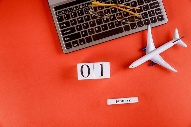 Calendrier du 1er janvier avec des accessoires sur le bureau de bureau de l'espace de travail sur le clavier de l'ordinateur, avion, fond rouge de lunettes