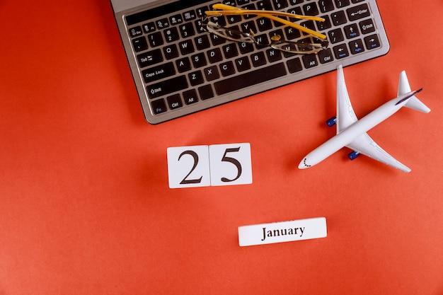 Calendrier du 25 janvier avec des accessoires sur le bureau de bureau de l'espace de travail sur le clavier de l'ordinateur, l'avion, les verres sur fond rouge