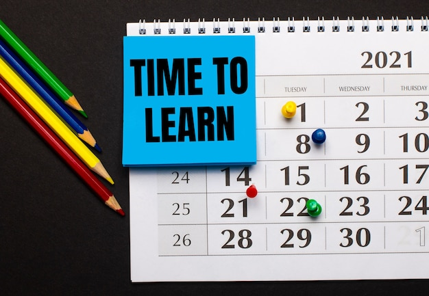 Le calendrier a du papier bleu clair avec le texte time to learn. crayons de couleur à proximité sur une surface sombre