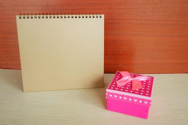 Calendrier de l'espace de travail avec coffret rose sur fond en bois.