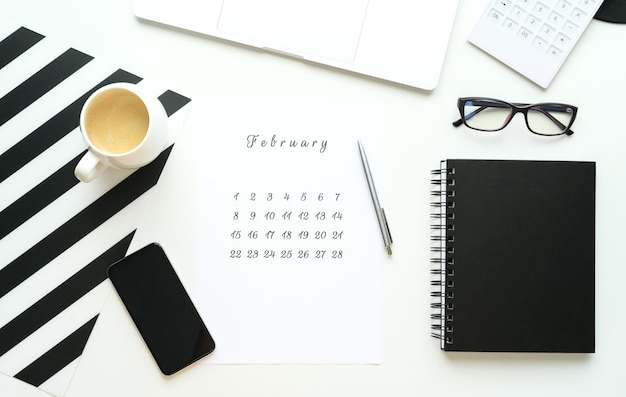 Calendrier de février sur ley plat de bureau blanc avec une tasse de café et un ordinateur portable