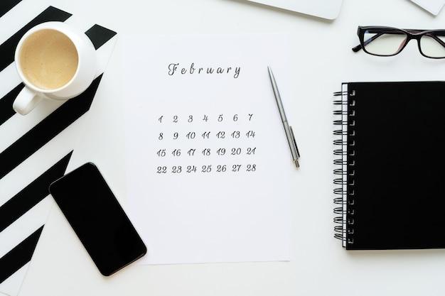 Calendrier de février sur plat de bureau blanc avec une tasse de café et un ordinateur portable, espace de travail