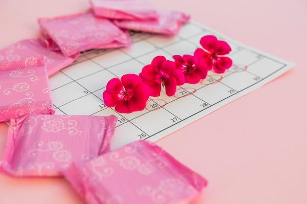 Calendrier avec des fleurs et des serviettes hygiéniques