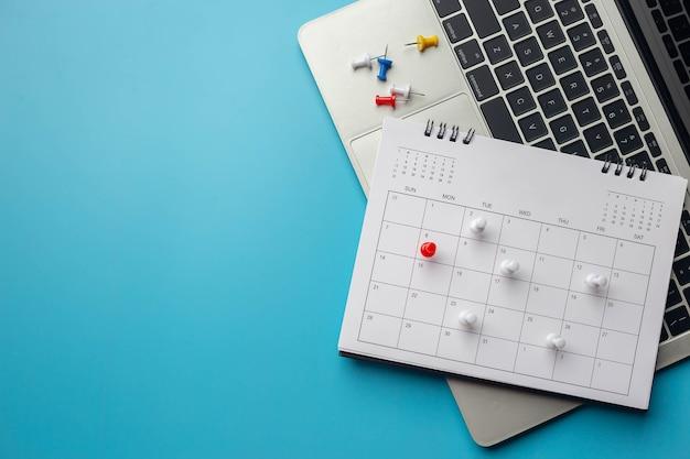 Calendrier sur fond bleu uni avec espace de copie, épinglé dans un calendrier sur le calendrier des réunions d'affaires, la planification des voyages ou le concept d'étape et de rappel du projet.