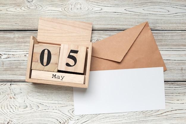 Calendrier en forme de cube en bois pour le 5 mai sur une table en bois