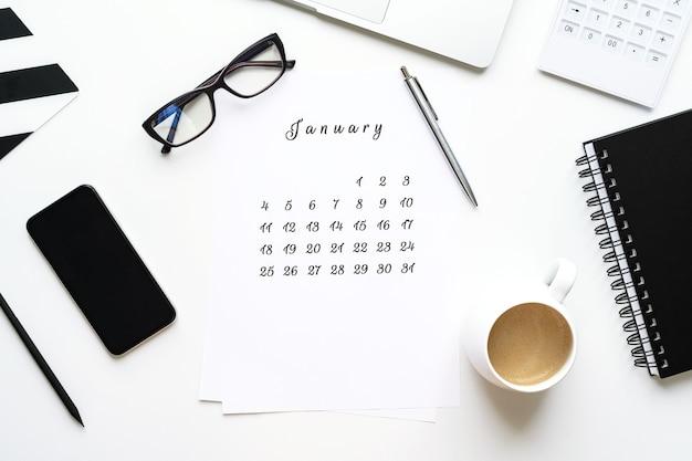 Calendrier de janvier sur le bureau blanc à plat avec une tasse de café et un espace de travail blanc pour ordinateur portable