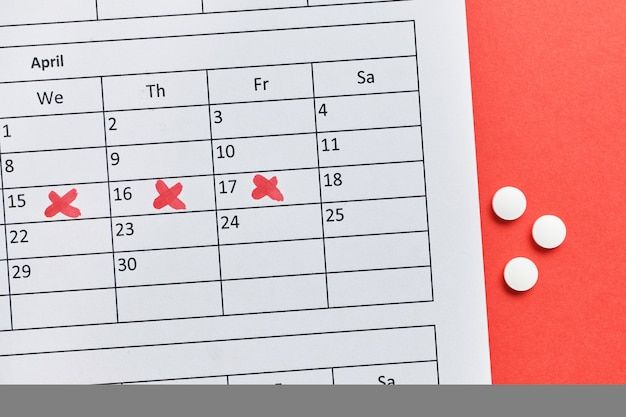 Un calendrier avec un marqueur marque l'autre jour avec des pilules hormonales