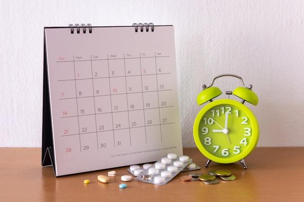 Calendrier et médicaments sur table.