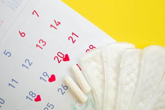 Calendrier menstruel avec des tampons en coton et des serviettes hygiéniques sur jaune