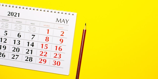 Sur un calendrier mural jaune 2021 et un crayon rouge. vue de dessus avec espace de copie.
