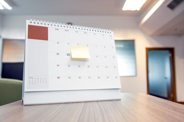 Calendrier avec note papier sur le bureau pour planificateur d'événements.
