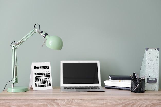 Calendrier avec ordinateur portable et papeterie sur table au bureau