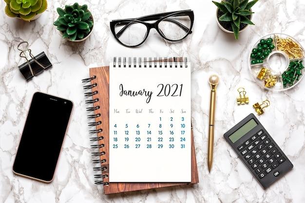 Calendrier ouvert janvier 2021, verres, tasse de café, stylo, smartphone, plantes succulentes sur table en marbre