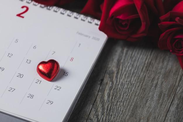 Calendrier en papier blanc placé sur un plancher en bois gris, vue de dessus et espace de copie, thème de la saint-valentin