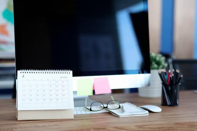 Calendrier de papier à feuilles mobiles debout près de l'ordinateur sur le bureau agrandi.