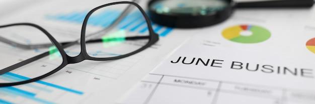 Calendrier papier pour juin couché sur le lieu de travail parmi les graphiques