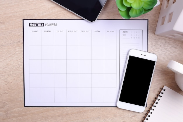 Calendrier de planificateur de smartphone écran blanc et fournitures de bureau sur fond en bois
