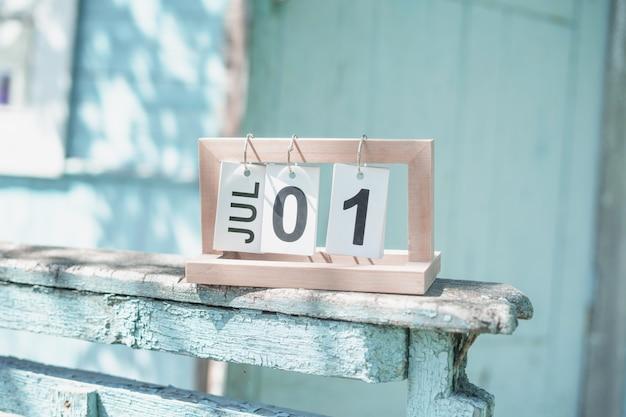 Calendrier pliant avec la date du 1er juillet sur l'ancienne balustrade en lambeaux. porche d'une maison de campagne minable aux couleurs bleu pâle.