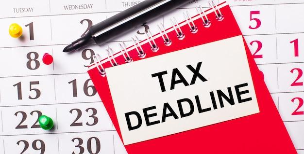 Sur le calendrier se trouve une carte blanche avec le texte date limite de taxe. a proximité se trouvent un bloc-notes rouge et un marqueur. vue d'en-haut.