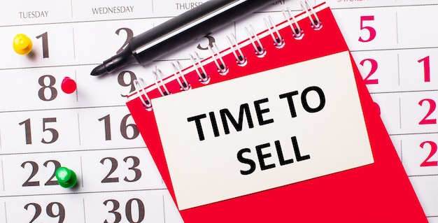 Sur le calendrier se trouve une carte blanche avec le texte time to sell. a proximité se trouve un bloc-notes rouge et un marqueur. vue d'en-haut