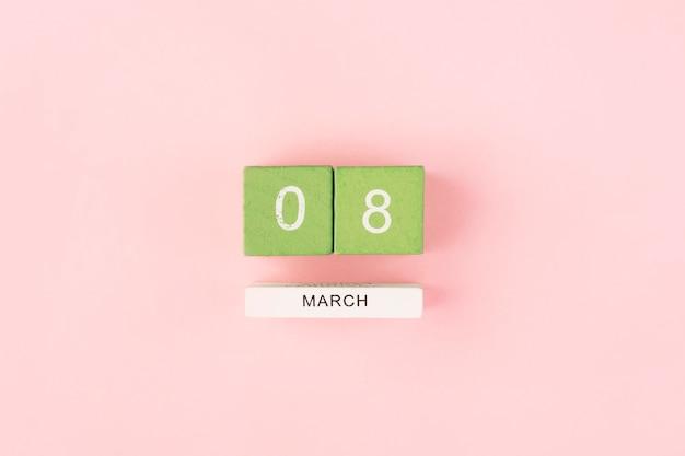 Calendrier vert le 8 mars sur une table rose, journée internationale de la femme