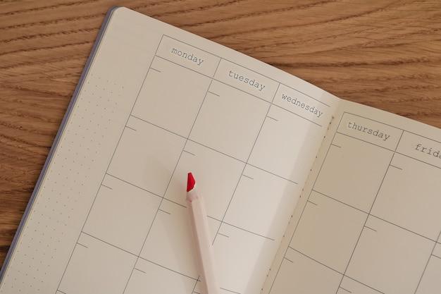 Calendrier vide et vierge et agenda ouvert vu de dessus avec un crayon à côté. planifier et faire le concept de liste. couleurs jaunes et grises de l'année.